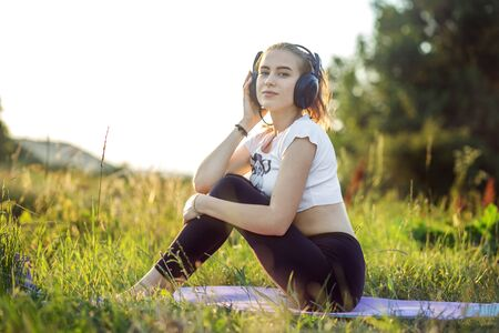 A teenager listens to the radio with headphones. The combination of nature and man. Concept for lifestyle, music, relaxation.
