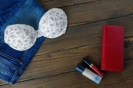 Bra, jeans and cosmetics and clutch bag. Copy space. Flat lay. The concept of clothing, accessories, shopping, lingerie. Фото со стока