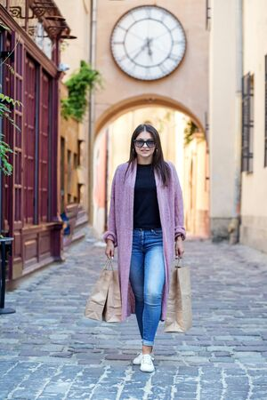 A young girl is walking with paper bags. Concept lifestyle, shopping, travel, time