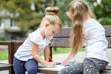 Children girls draw and play. The concept of school, study, education, friendship, childhood.