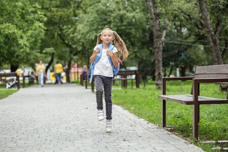Child girl runs from school with a backpack. The concept of school, study, education, friendship, childhood