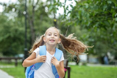 Child girl runs and smiles. Schoolgirl with backpack. The concept of school, study, education, friendship, childhood