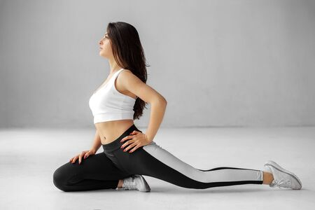 Place for text. Young adult girl is engaged in stretching. Sportswear. The concept of sports, healthy lifestyle, fitness, stretching