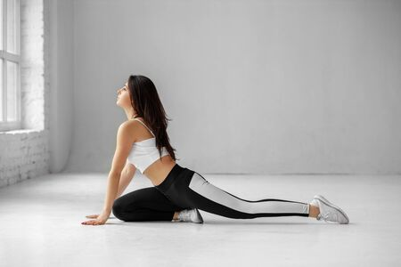 A young adult girl is engaged in aerobics. Sportswear. Place for text. The concept of sports, healthy lifestyle, fitness, stretching