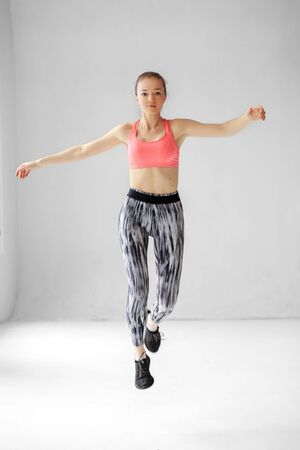 Young adult girl makes a jump in the gym. Sportswear. Place for text. The concept of sports, healthy lifestyle, fitness, stretching 写真素材