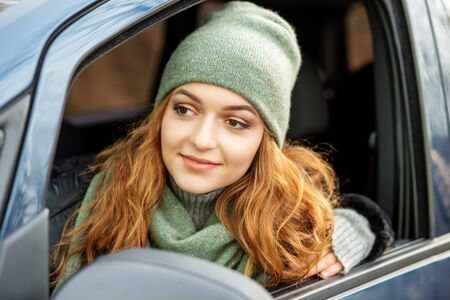 Young woman driving a car. Green hat and scarf. Concept lifestyle, autumn, winter, auto driver. Zdjęcie Seryjne
