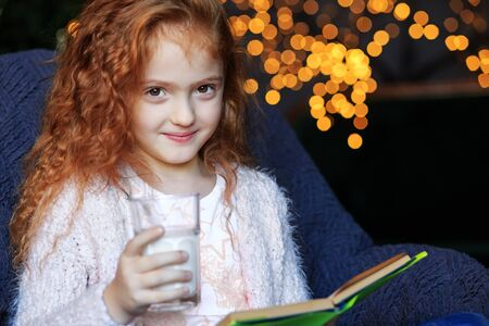Girl is smiling and reading a book on Christmas Eve. Tasty milk. The concept of holidays, merry christmas, winter and childhood.