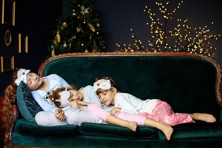 Three girls children sleep in pajamas on the couch. The concept of Merry Christmas, holidays, New Year, family and gifts