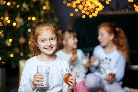 Children drink milk and eat cookies. Sisters in pajamas. The concept of Merry Christmas, holidays, New Year, family and gifts.