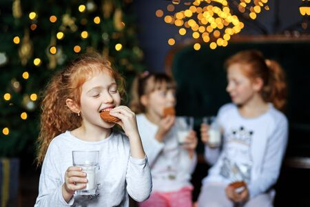 Children drink milk and eat cookies on Christmas Eve. Sisters in pajamas. The concept of Merry Christmas, holidays, New Year, family and gifts.