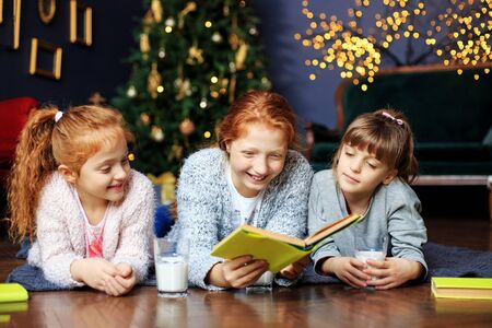Three kids girls are reading a book on Christmas Eve. The concept of Merry Christmas, holidays, New Year, family and gifts.
