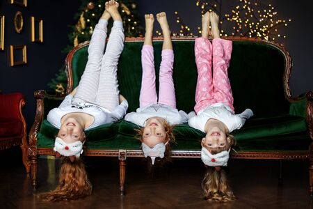 Three children have fun on Christmas Eve. The concept of Merry Christmas, holidays, New Year, family and gifts.