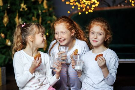 Children communicate near the Christmas tree. The sisters drink milk and laugh. Sisters in pajamas. The concept of Merry Christmas, holidays, New Year, family and gifts.