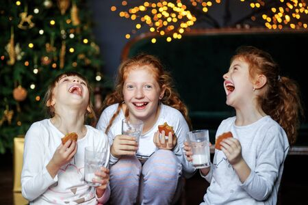 Children communicate near the Christmas tree. Sisters drink milk, eat cookies. Loud laughter. Sisters in pajamas. The concept of Merry Christmas, holidays, New Year, family and gifts. 写真素材