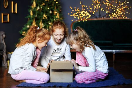 Three children open a gift box. Sisters in pajamas. The concept of Merry Christmas, holidays, New Year, family and gifts
