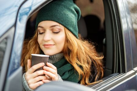 Woman driver drinks coffee in a car. Concept of driving a car, exam for a drivers license, car purchase and insurance.