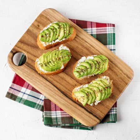 Tasty sandwiches with feta and avocado on the kitchen board. Food concept. Square. Flat lay.