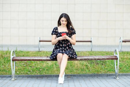 A young girl reads social networks and drinks coffee. Dress and sneakers. The concept of a lifestyle, a break, students and communication on the Internet.