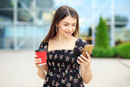 A young woman reads social networks and drinks coffee. The concept of a lifestyle, a break, students and communication on the Internet.