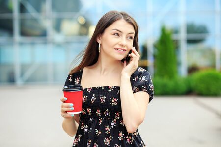 A young woman speaks on the phone and drinks coffee. The concept of a lifestyle, a break, students and communication on the Internet.
