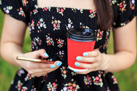 Coffee in a red plastic glass. Smartphone in female hands. The concept of a lifestyle, a break, students and communication on the Internet.