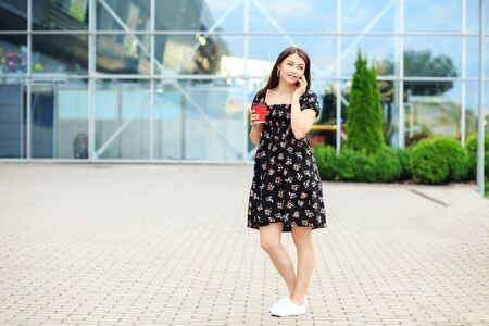 A young woman speaks on the phone and drinks coffee. Dress and sneakers. The concept of a lifestyle, a break, students and communication on the Internet.