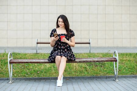 A young girl reads the news and drinks coffee. Dress and sneakers. The concept of a lifestyle, a break, students and communication on the Internet.