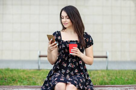 A young woman reads the news and drinks coffee. The concept of a lifestyle, a break, students and communication on the Internet.