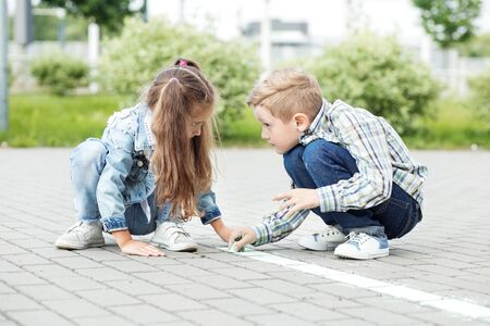 Little brother and sister draw with chalk on the pavement. The concept of childhood, back to school, friendship.