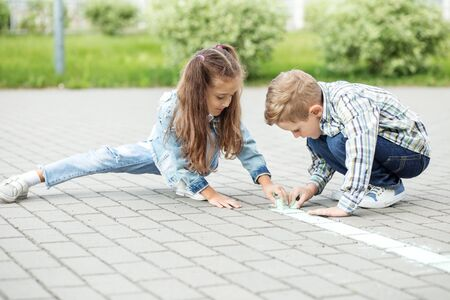 Little girl and boy draw with chalk on the pavement. The concept of childhood, back to school, friendship.
