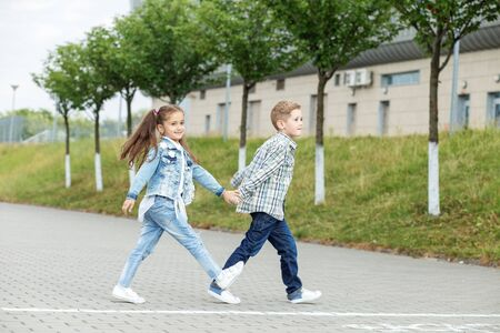 Little brother and sister walk holding hands. The concept of childhood, back to school, friendship and family.
