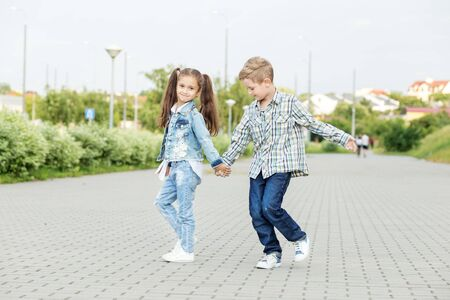 Little boy and girl go holding hand. The concept of childhood, back to school, friendship and family. 写真素材