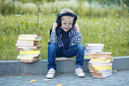 Little boy in headphones. Lots of books. Back to school. The concept of learning, school, mind, lifestyle and success.