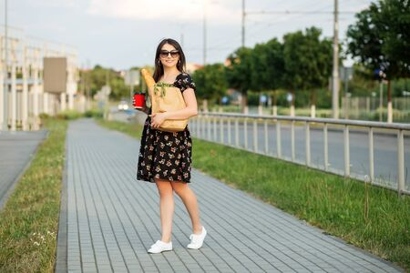 A young woman holds a grocery bag and a glass of coffee. Dress in a flower. The concept of shopping, eco shopping, lifestyle. 写真素材