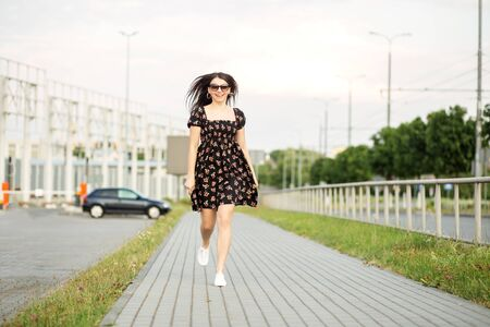 An adult smiling woman walks down the street in a stylish dress. The concept of the style of life, urban, happiness and active life.