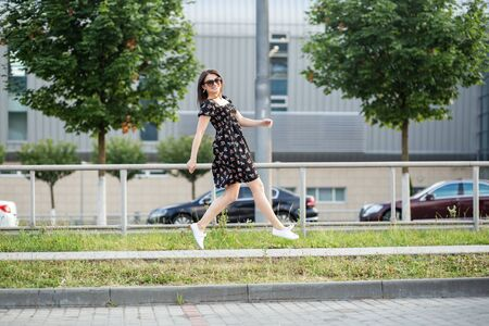 Adult brunette woman running down the street in a stylish dress. The concept of the style of life, urban, happiness and active life.