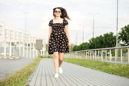Adult smiling girl is walking down the street in a summer dress. The concept of the style of life, urban, happiness and active life.
