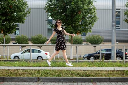 An adult smiling woman bounces down the street in a stylish dress. The concept of the style of life, urban, happiness and active life.