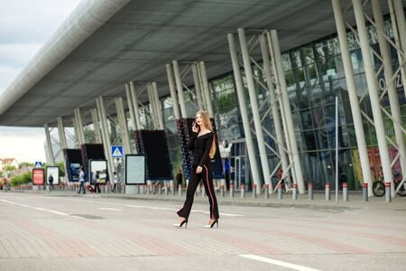Successful woman walks on a crosswalk. Communicate by mobile phone. Concept for lifestyle, business, movement, motivation.