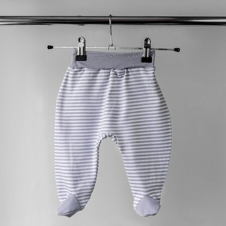 Gray striped pants for a newborn. The concept of clothes, motherhood and newborn.