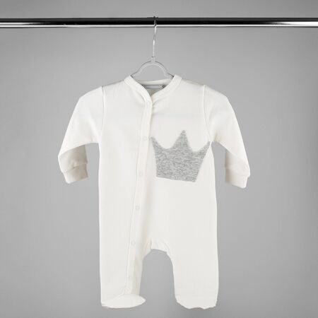 White clothes for a newborn hanging on a hanger. The concept of clothes, motherhood and newborn.