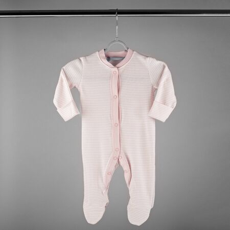 Pink striped clothes for a newborn hanging on a hanger. The concept of clothes, motherhood, fashion and newborn.