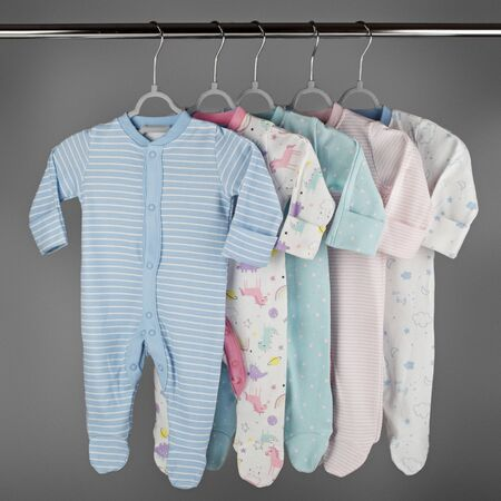 Color set of clothes for newborn baby hanging on a hanger. The concept of clothes, motherhood, fashion and newborn.