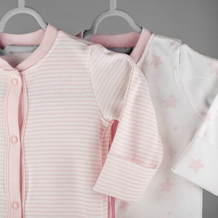Pink striped clothes for a newborn hanging on a hanger. Square. The concept of clothes, motherhood, fashion and newborn.