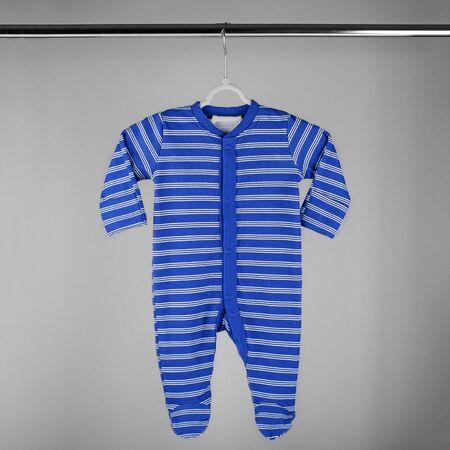 Donkerblauw gestreepte kleding voor een pasgeborene hangend aan een hanger. Het concept van kleding, moederschap, mode en pasgeboren.