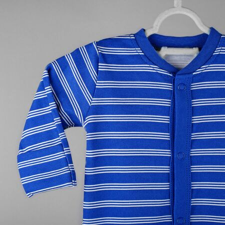 Dark blue striped baby clothing hanging on a hanger. The concept of clothes, motherhood, fashion and newborn. 写真素材