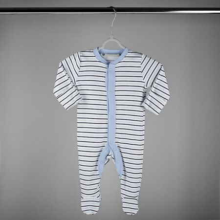 Blue striped clothes for a newborn hanging on a hanger. The concept of clothes, motherhood, fashion and newborn. 写真素材