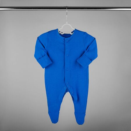 Dark blue clothes for a newborn hanging on a hanger. The concept of clothes, motherhood, fashion and newborn.