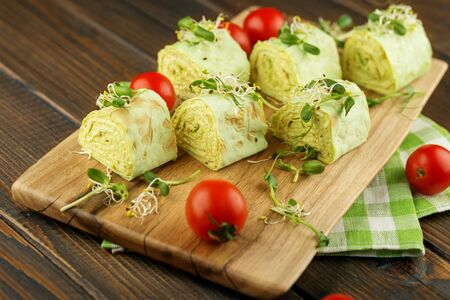 Tasty rolls with pita bread, cheese and micro greens and sauce. Kitchen board and napkin. The concept of food, catering, banquet.
