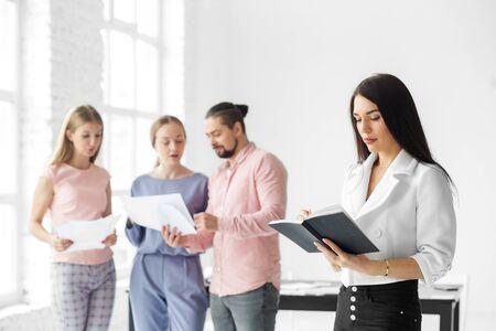 看笔记本的女商人。一天的任务清单。企业家,业务,团队合作和成功的概念。
